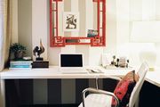 A red chinoiserie mirror hung on striped walls above a white desk