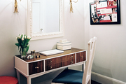 A white chair and a wooden desk paired with wheat-sheaf sconces