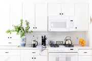 A white kitchen with coffee and oranges.