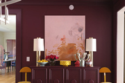 Pink entry and hallway with burgundy credenza and artwork