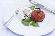 A detail of a tomato, basil, and mozzarella salad.