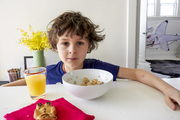 A breakfast scene with cereal bowl, juice glass, and brightly colored napkins
