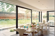Rectangular white tables in a dining space with retractable glass doors