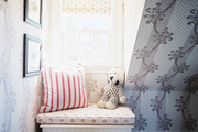 A window seat in a bedroom with patterned wallpaper
