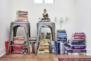 Colorful books are stacked below and on top of metal stools.