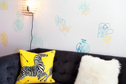 Colorful scribbled wall surrounding a lush black couch with fun throw pillows.