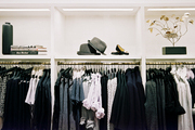 Decorative accessories on shelves above clothing on hangers