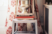 A boxwood-topped silver urn on a stack of books