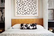 A framed artwork hung above a burlwood headboard