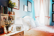 A faux-bamboo bedside table and a white headboard in a bedroom with blue walls