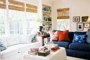 A white ottoman surrounded by white and blue couches and bamboo shades