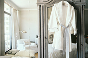 A gray mirrored armoire against a wall of mirrors