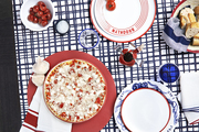 A California Pizza Kitchen pizza on a graphic tablecloth with red, white, and blue dinnerware