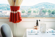 Red banding on white curtains above a light-gray dining chair
