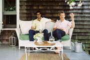 Jaithan Kochar and Eddie Ross seated on a wicker settee on the porch of their New York home