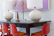Red midcentury dining chairs at a table with floor lamps and sunburst ephemera