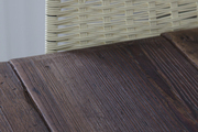 Metal wicker chair against brown stained wooden table.