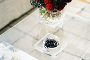 A vase of flowers on a see-through coffee table