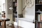 Large scale art hanging above built in bench with matching bookshelf in grey dining room.