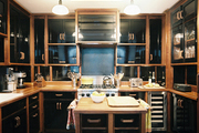 Black-and-wood cabinetry, wood countertops, and herringbone floors in a kitchen