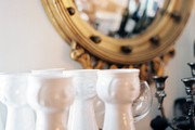 A collection of cheeky white glasses beside a gold convex mirror