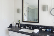 A bathroom with stone countertops and penny-tile floors