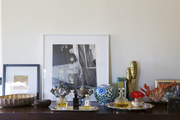 Framed art, antique objets, and perfume bottles on a bedroom bureau