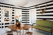 Horizontally striped walls paired with a green antique settee and a round tulip-style table