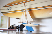 A surfboard above a model sailboat