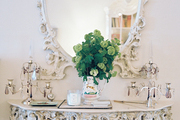 An ornate mirror and table against white walls