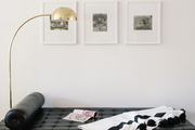 A streamlined gallery wall and day bed and floor lamp,