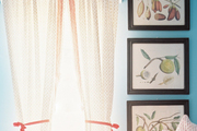 A trio of botanical prints hung beside patterned curtains