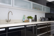 A sleek counter with onyx storage cabinets, contrasting countertops, a stainless steel sink, appliances, and glass pantries.