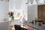 A colorful dining area and window seating featuring colorful glass pots.