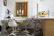 An art filled dining table, kitchen island, and an animal print rug in dining room.