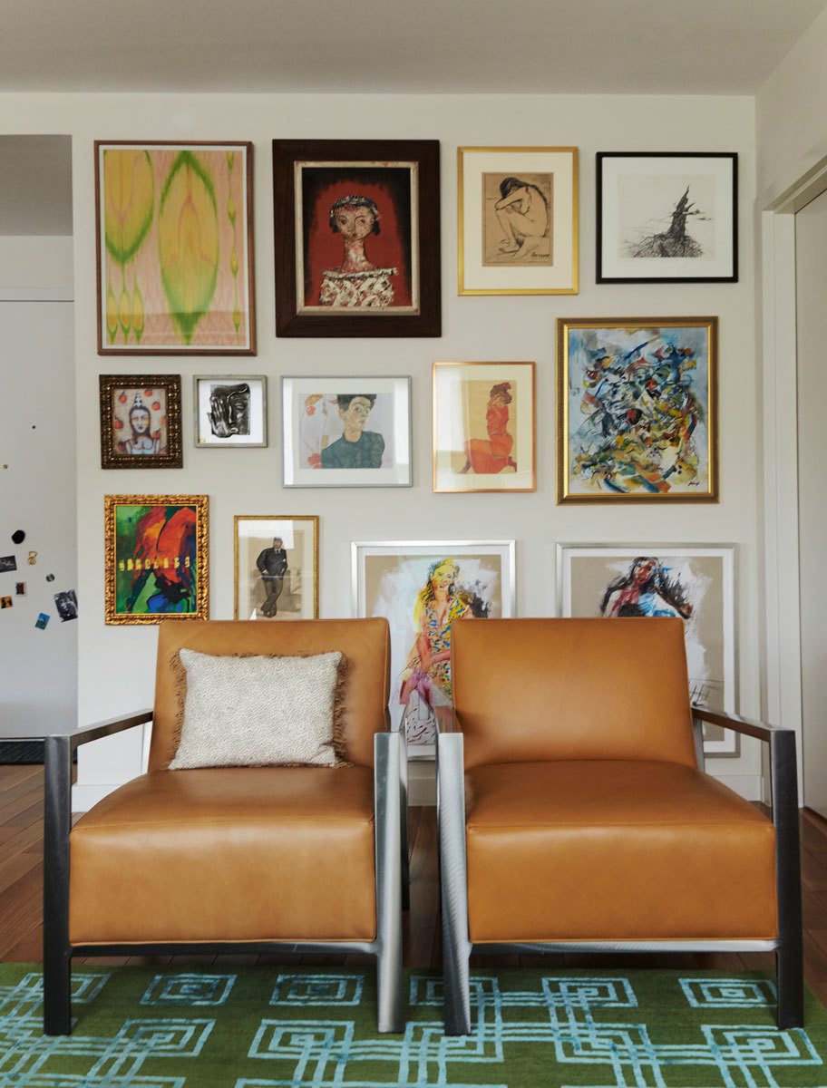 The couple's art collection, arranged gallery style, complements a sleek pair of Room & Board armchairs.