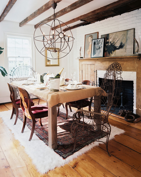 The dining room's rustic features are cleverly juxtaposed with midentury artworks. An oversized spherical light fixture offers a geometric counterpoint to the ceiling's linear beams.