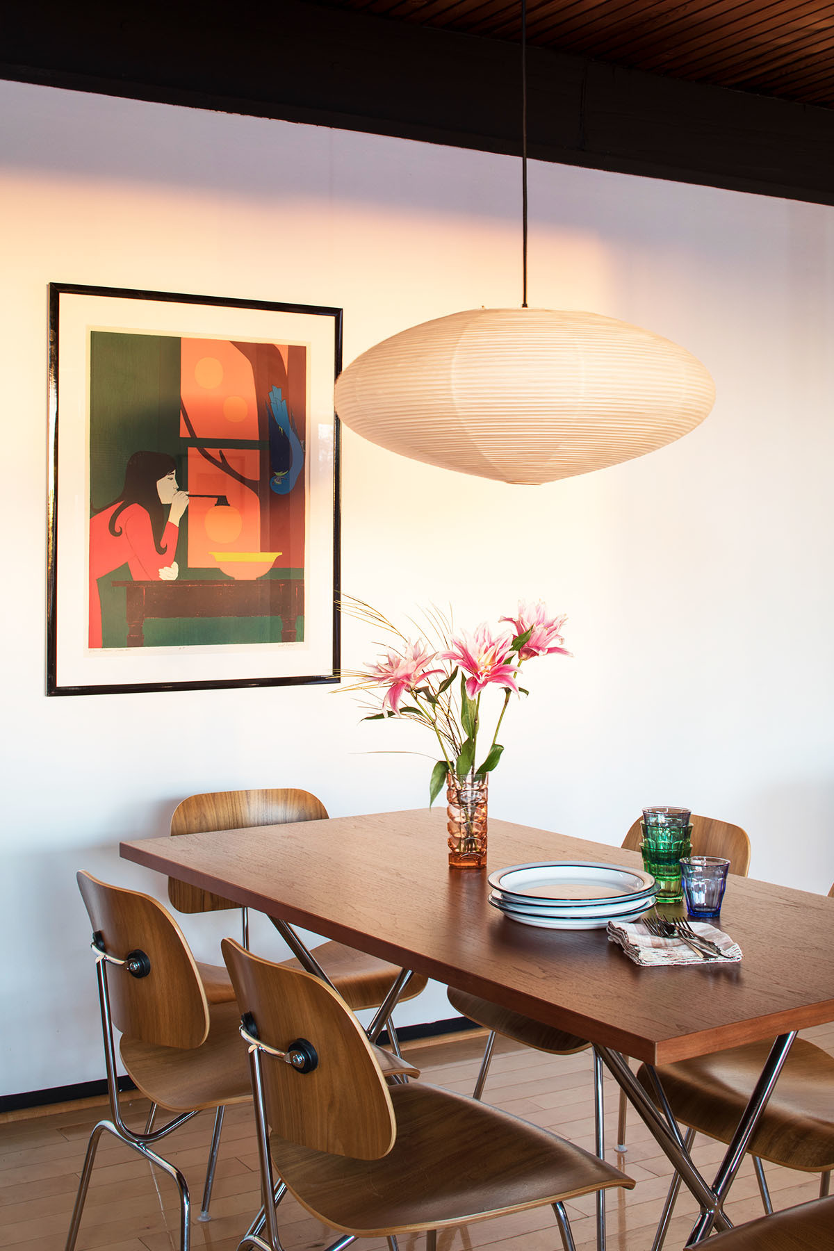 A classic Noguchi pendant light and George Nelson dining table complete the pared-back dining space, located adjacent to the kitchen. Eames for Herman Miller Dining Chairs | Rosalind Arcoroc Vintage Glassware | Will Barnet Artwork.