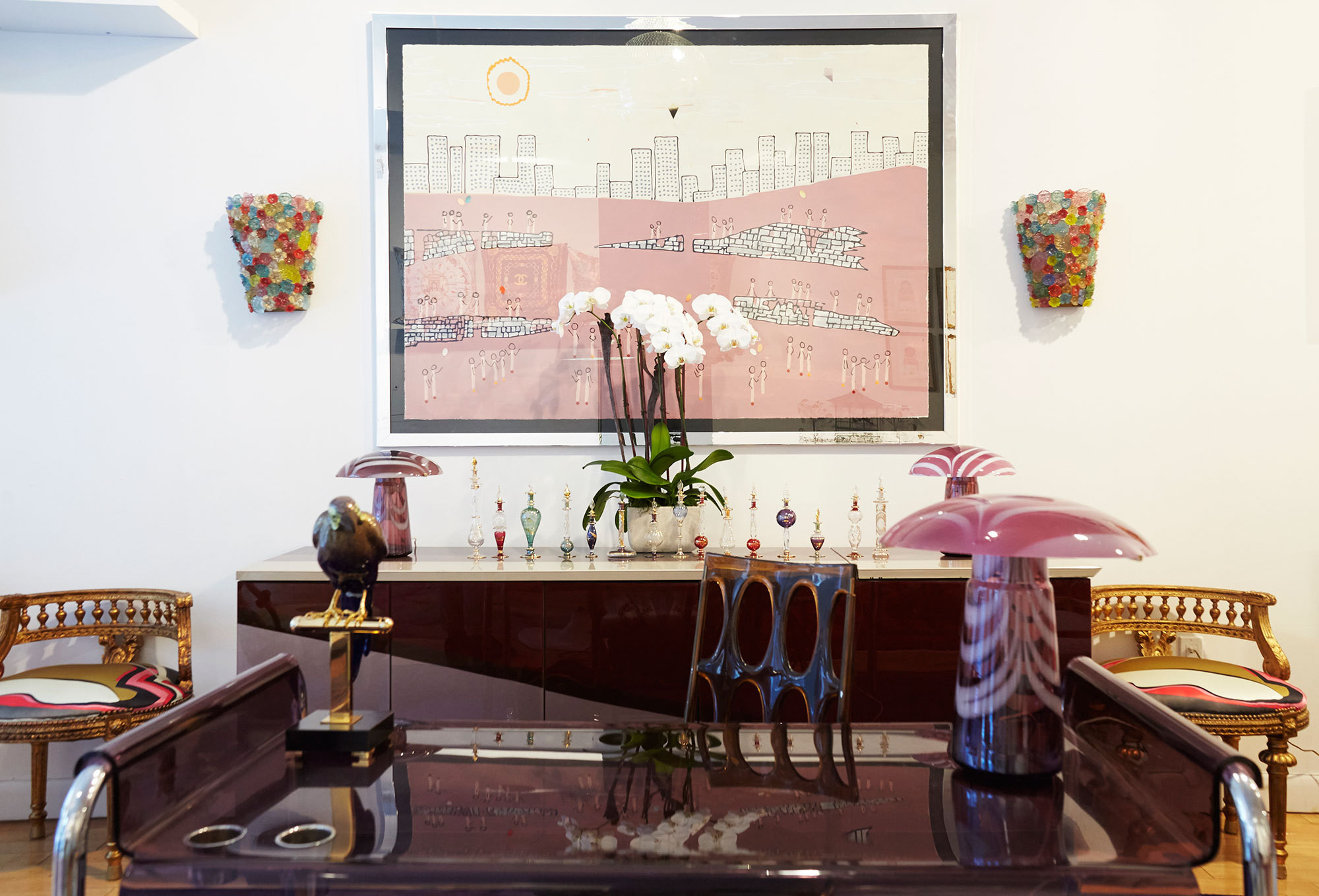 In Bikoff's showroom, a vintage Italian lucite desk and Pierre Cardin credenza are framed by a pair of gilded French Empire stools in Pucci silk.