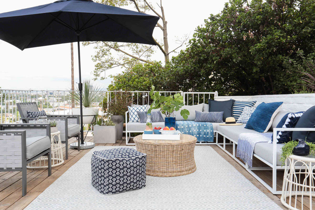 The living area of Emily Henderson's newly transformed deck, featuring an indoor-outdoor rug, pouf, umbrella, and patio chairs from Target's Threshold collection. For more product information, see slideshow below.