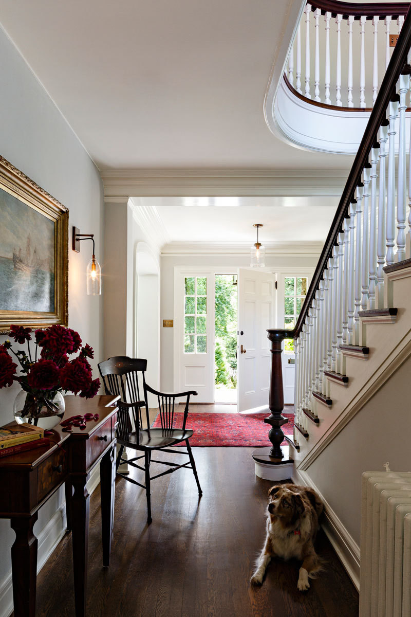 A gracious set of stairs leads upward from the light-filled entry.