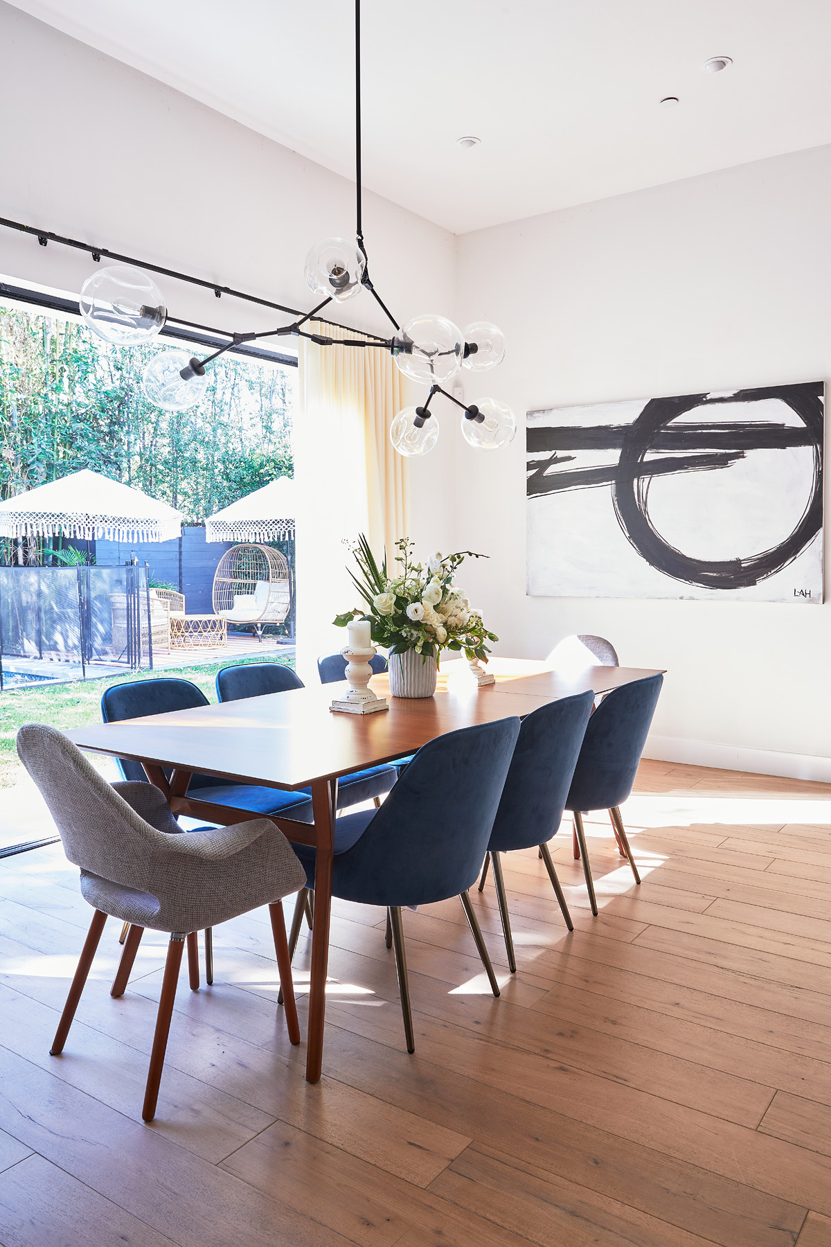 The dining room is a modern take on mid-century elegance.West Elm Expandable Dining Table |West Elm Mid-Century Upholstered Dining Chair | Lauren Kleinman Abstract Painting |Dot & Bo 7-Globe Bubble Chandelier |Ophelia & Co.Bethea Stone Candlestick.