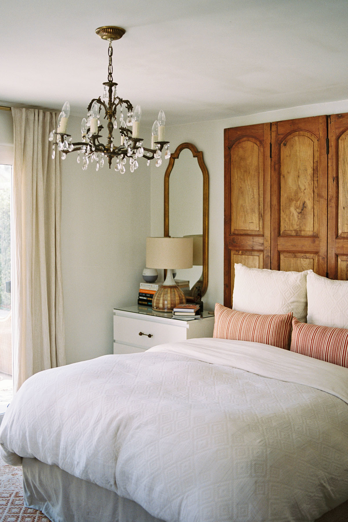Madison repurposed a set of old church doors, sourced via the Long Beach Flea Market to create a custom headboard in the couple's bedroom. Rejuvenation Bedding | Ralph Lauren Throw Pillows | Melrose Flea Market Vintage Mirror | IKEA Nightstand | Anthropologie Hardware.