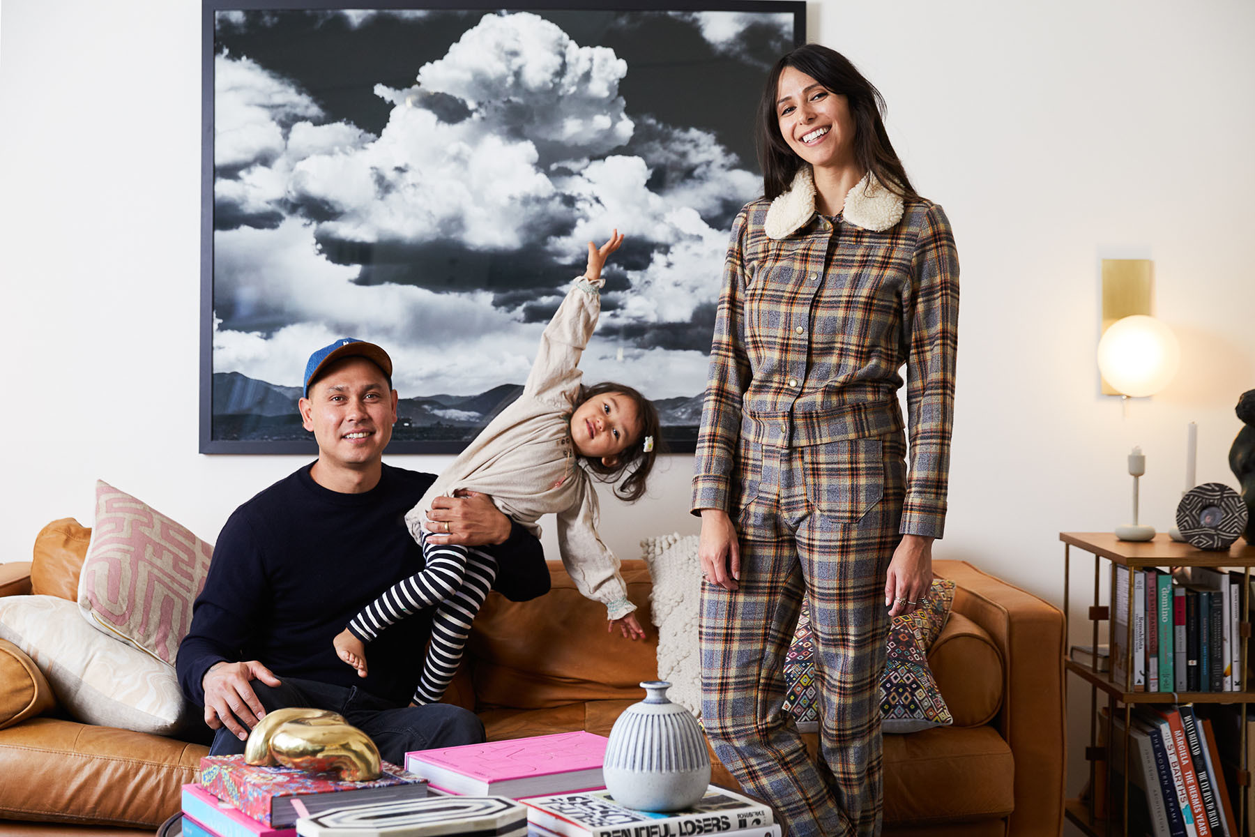 Eric, the couple's daughter Tallieand Angela are right at home in their light and bright living room. ArticleSofa |Minted Photo|St. Frank Pillows |Jayson Home Gold Snake | Bone Inlay Tray |Hudson Valley Lighting Sconce |Sonder Side Table| Angela wearsLykke Wulf pants and jacket.