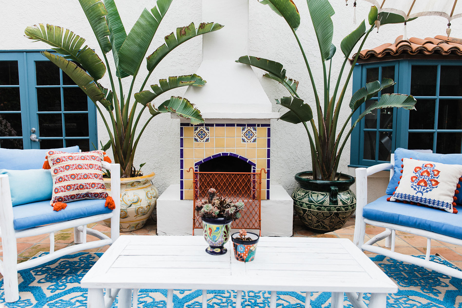 A tiled hearth and a Moroccan-inspired palette make Shiza Shahid's L.A. home a respite from the daily grind. Artisan Made Armchairs | Living Spaces Outdoor Rug | Antique Fireplace Guard | Antique Cocktail Table | Vintage Vases | Vintage Planters.