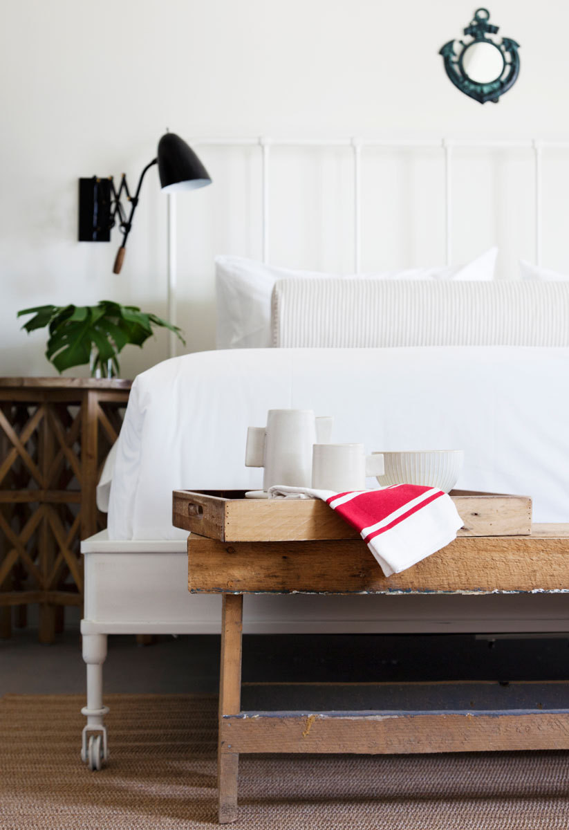 Metal-framed beds sourced from RHare madewith posh Frettelinens. A wood bench was found at a local antiques shop.