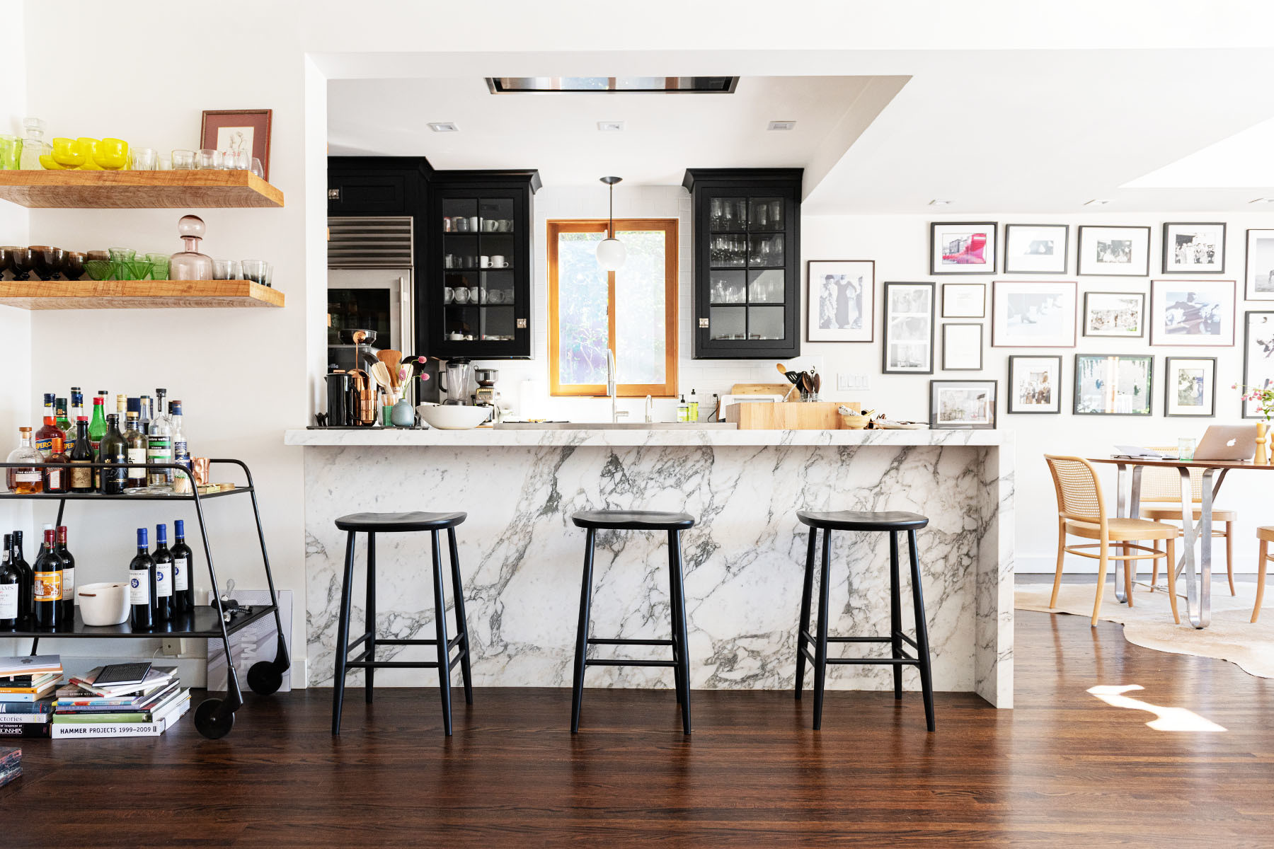 Eyewear designer Kyly Rabin fills her Silver Lake home with a refreshing blend of minmal furniture and family heirlooms. Viking, Miele, Sub-Zero Wolf, Breville Appliances | Custom Cabinetry | Custom Marble Kitchen Island | A+R Bar Stools | Custom Beechwood Floating Shelves | Roost Bar Cart | Tom Dixon Assorted Barware | Cedar & Moss Light Fixture | Design Within Reach Dining Chairs | Lawson Fenning Dining Table | Vintage Frames.
