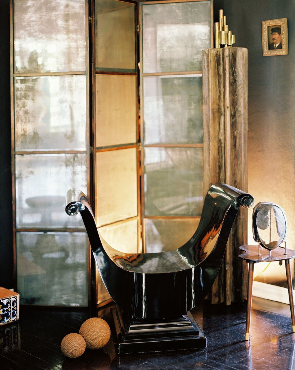 A black lacquer bench, an antique mirror, and a steel screen round out Straus' reading area.