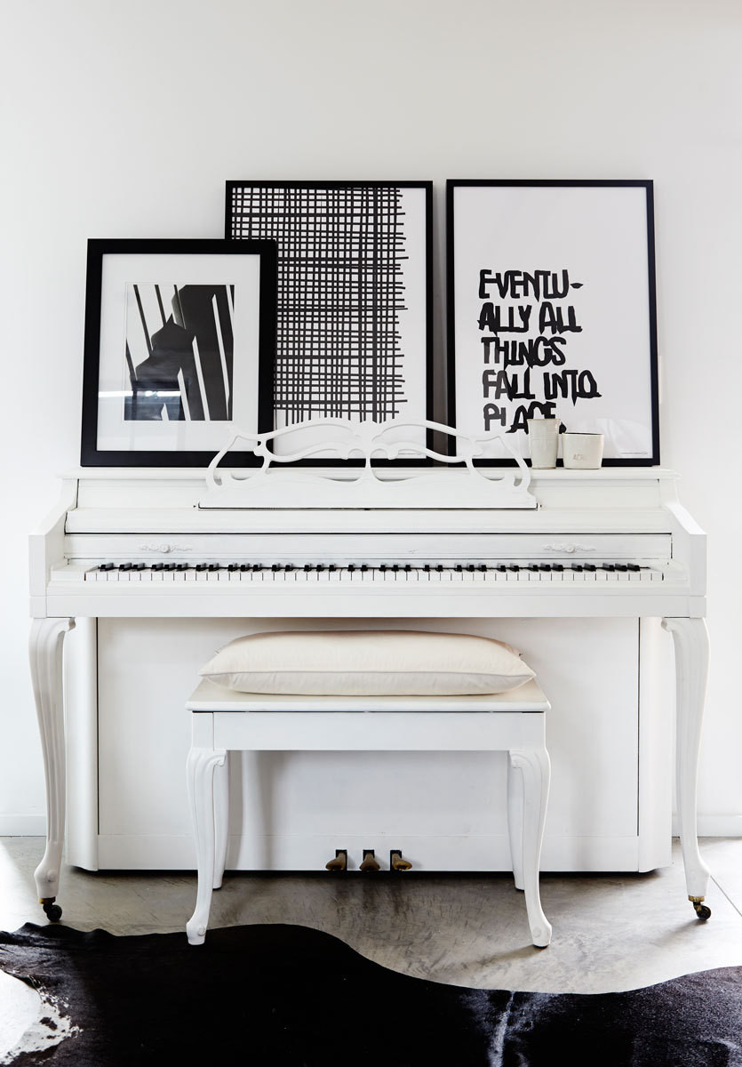 The family's piano, which was coated in a milky-white hue by homeowner Erin Crotty, gets added punch from a trio of black-and-white art prints.