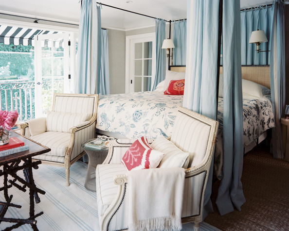 The master suite boasts a slim, yet statement-making canopy bed draped in serene, soft blue fabric panels. An intimate seating area is nestled at the foot of the bed.